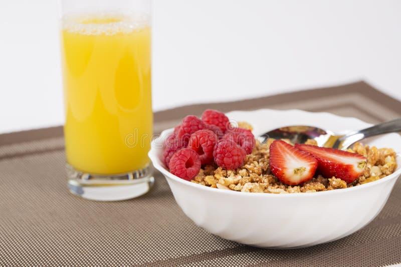 Cereali dorati con i halfs ed il succo del berrie fotografia stock libera da diritti