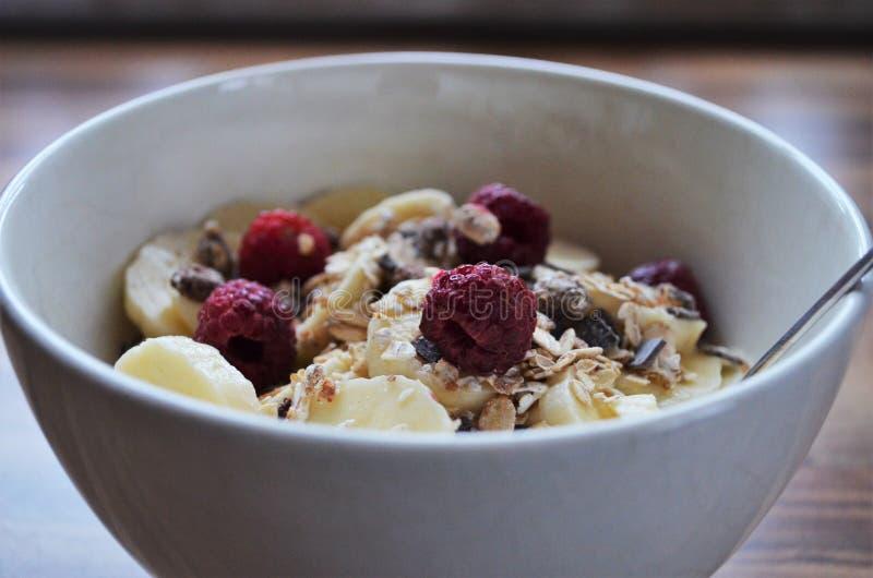 Cereali in una ciotola con le banane ed i lamponi fotografia stock