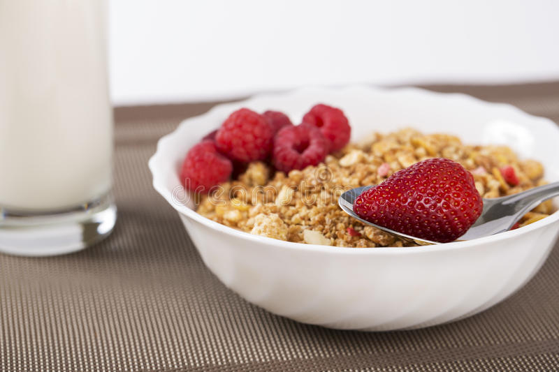 Cereals in bowl with strawberries and raspberries royalty free stock photo