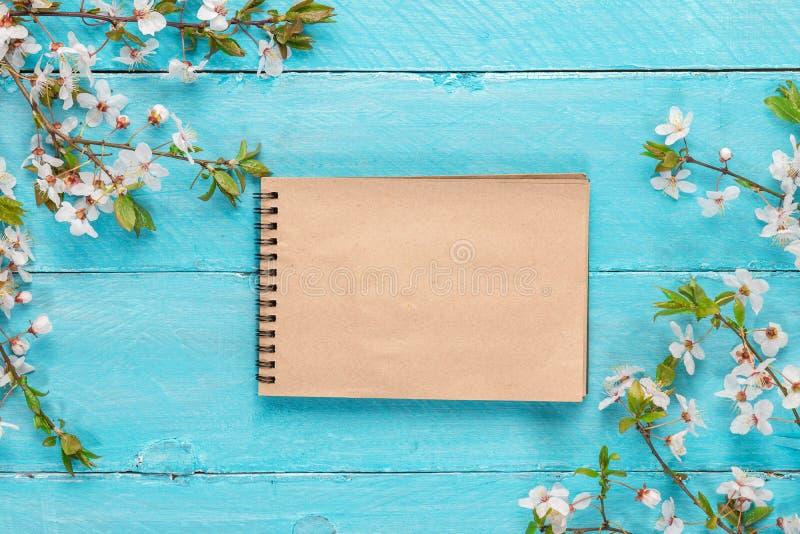 Cereja das flores da beira da mola que floresce com o caderno de papel vazio no fundo de madeira azul Vista superior fotografia de stock