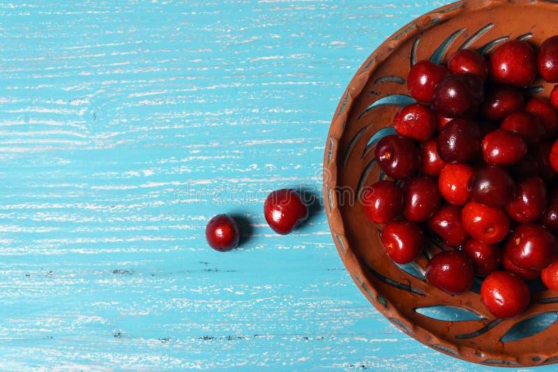 Cereja doce vermelha em uma placa da argila em uma tabela de madeira de turquesa imagem de stock royalty free