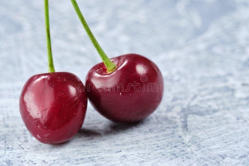 Cereja dois doce fresca em um fundo cinzento Fim acima imagens de stock