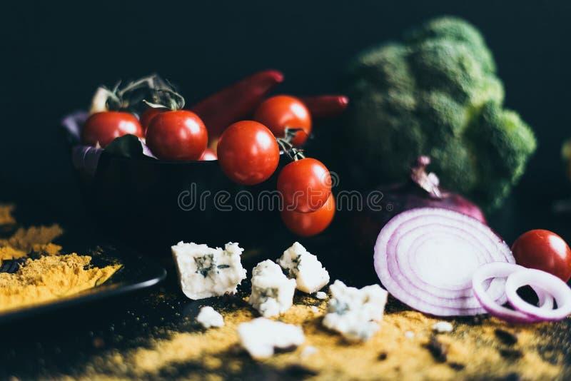 Cereja fresca deliciosa dos tomates e pimentas de pimentão encarnados em um prato preto que encontra-se em uma placa de corte de  foto de stock royalty free