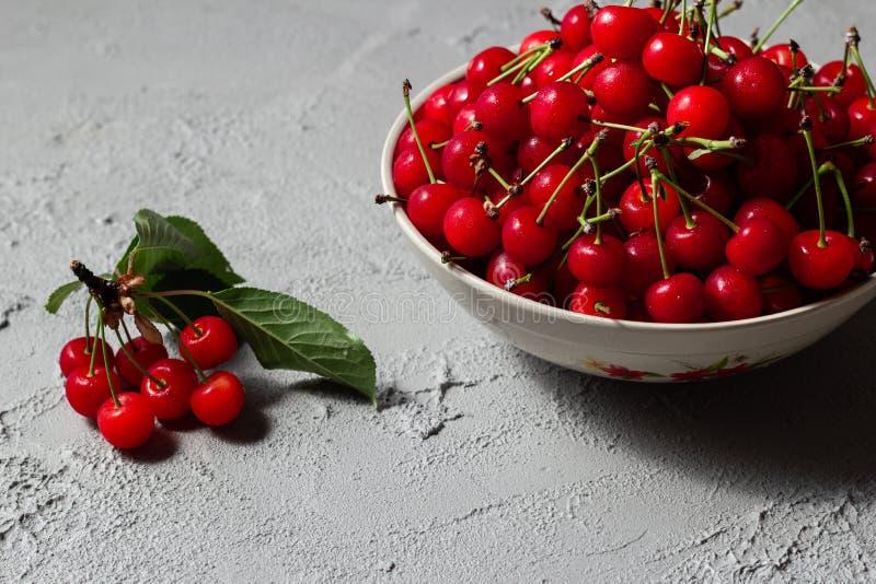 A cereja fresca em uma placa com verão floresce em um fundo concreto Bagas maduras frescas Cerejas fotos de stock royalty free