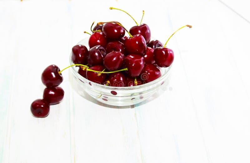 Cereja fresca na placa de vidro no fundo branco de madeira Cerejas maduras frescas foto de stock royalty free