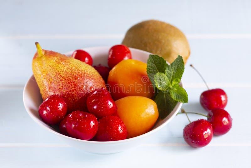 Cereja vermelha, abricós, pera de Forelle com hortelã fresca em uma bacia branca fotos de stock