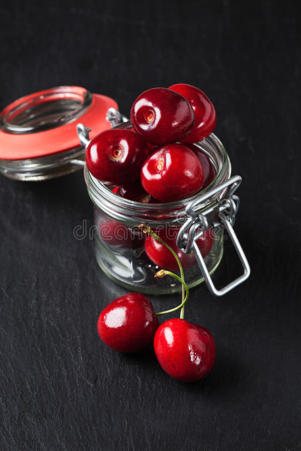 Cerejas doces em preservar o frasco na ardósia foto de stock royalty free