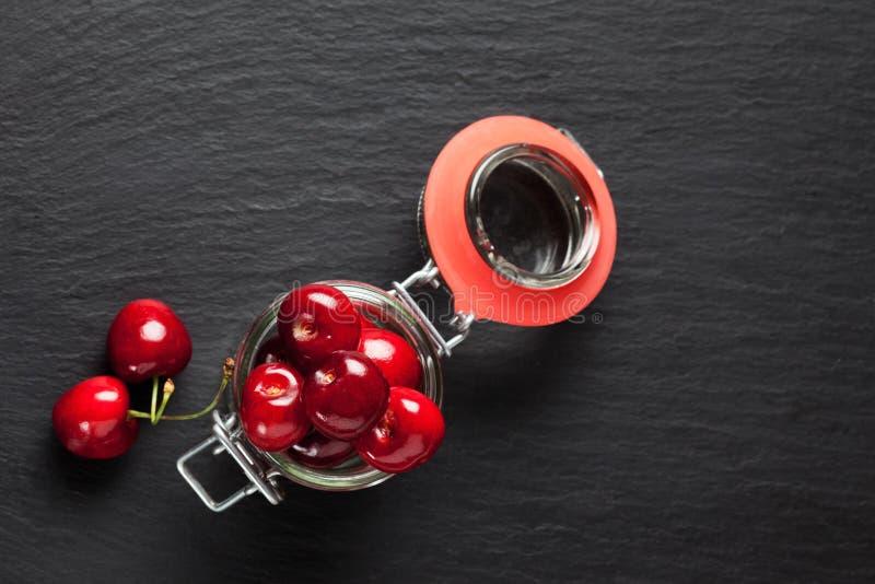 Cerejas doces em preservar o frasco na ardósia imagens de stock