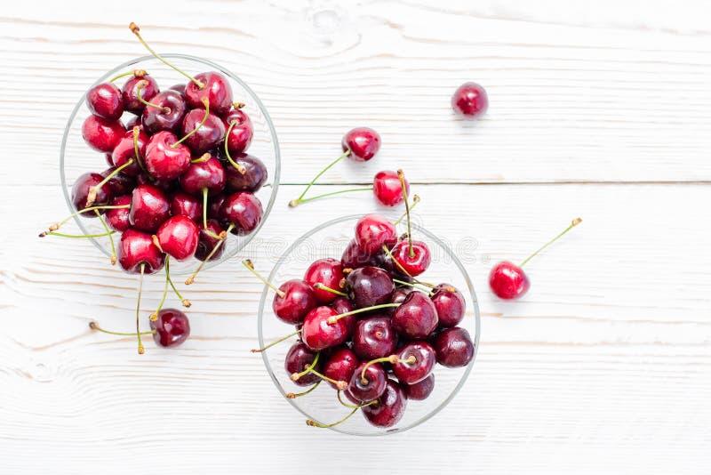 Cerejas doces maduras frescas em gotas da água em umas bacias em uma tabela de madeira branca Copie o espa?o foto de stock royalty free