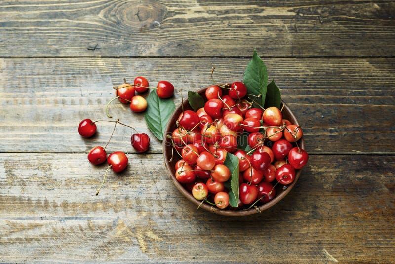 Cerejas doces doces vermelhas em uma placa em um fundo de madeira Vista de acima fotografia de stock