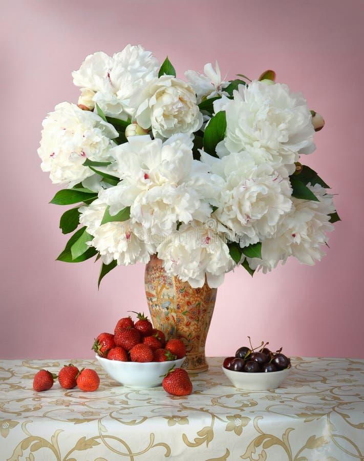 Cerejas e morangos maduras com o ramalhete das peônias fotografia de stock