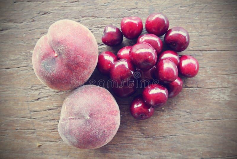 Cerejas e pêssegos vermelhos maduros na tabela de madeira, retro filtrado foto de stock royalty free