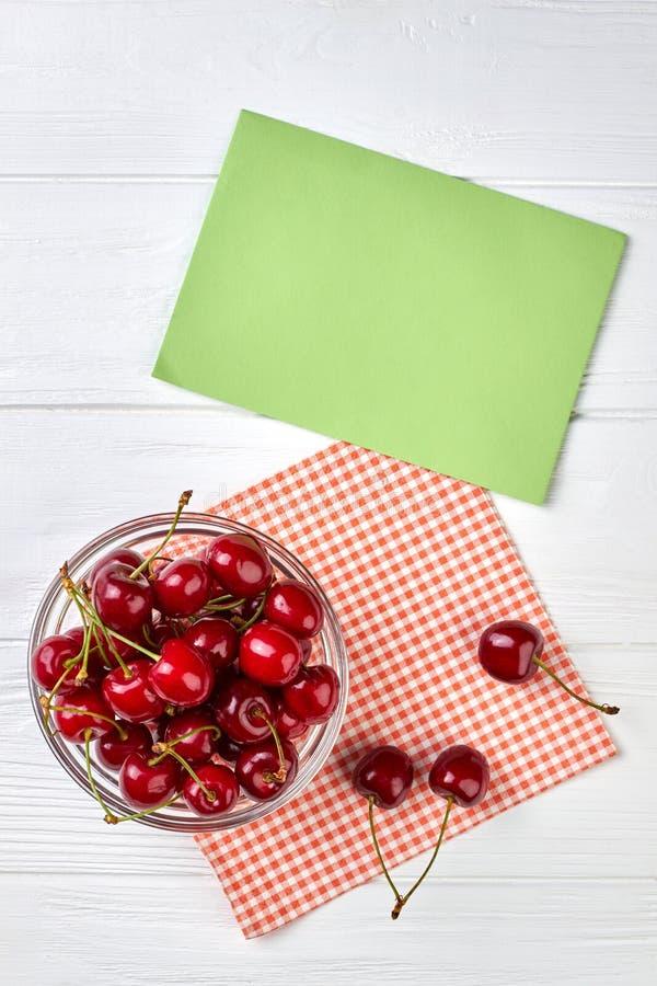 Cerejas frescas e cartão de papel vazio imagens de stock