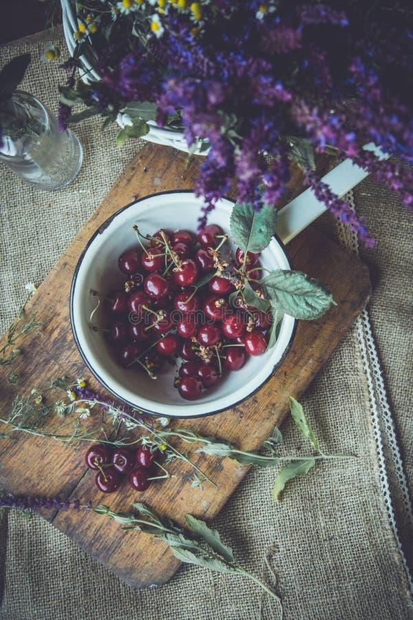 Cerejas frescas em um trencher de madeira fotos de stock