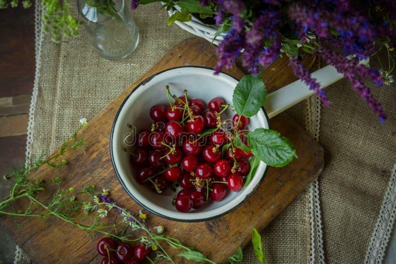Cerejas frescas em um trencher de madeira foto de stock