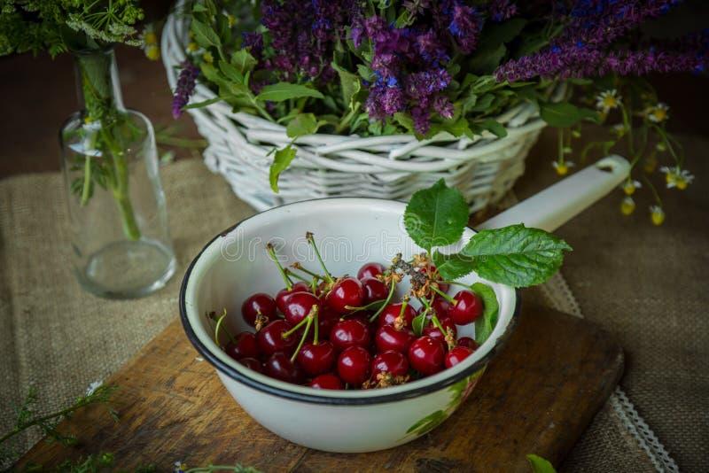Cerejas frescas em um trencher de madeira imagens de stock