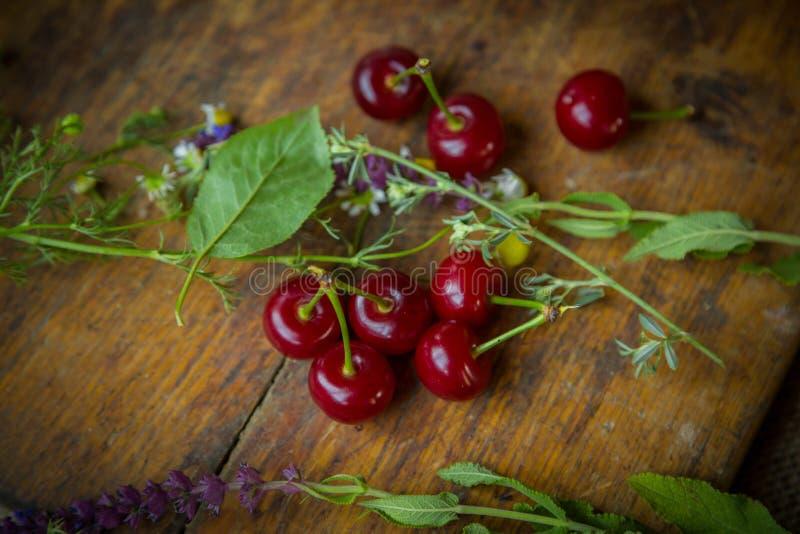 Cerejas frescas em um trencher de madeira imagem de stock