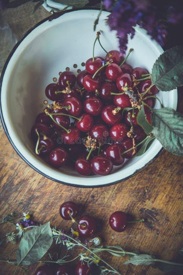 Cerejas frescas em um trencher de madeira imagens de stock royalty free
