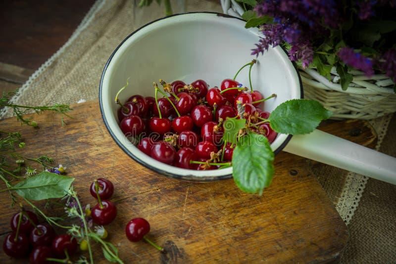 Cerejas frescas em um trencher de madeira fotografia de stock royalty free