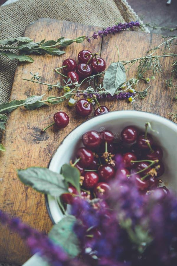 Cerejas frescas em um trencher de madeira fotografia de stock