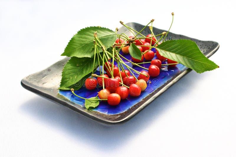 Cerejas frescas em uma placa imagem de stock royalty free