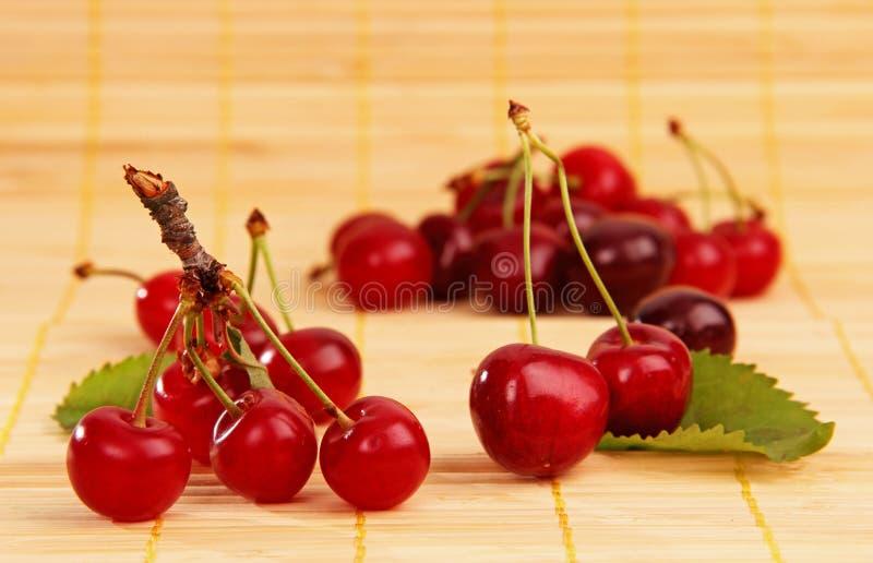 Cerejas frescas na tabela. Patas com lea verde fotos de stock