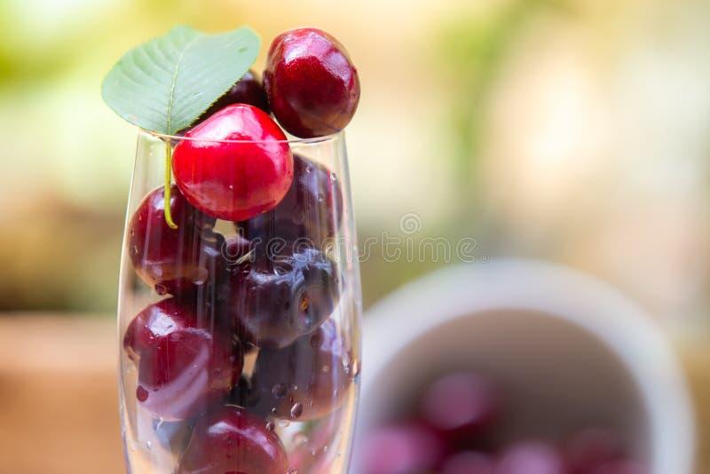 Cerejas frescas no vidro com folha fotos de stock royalty free