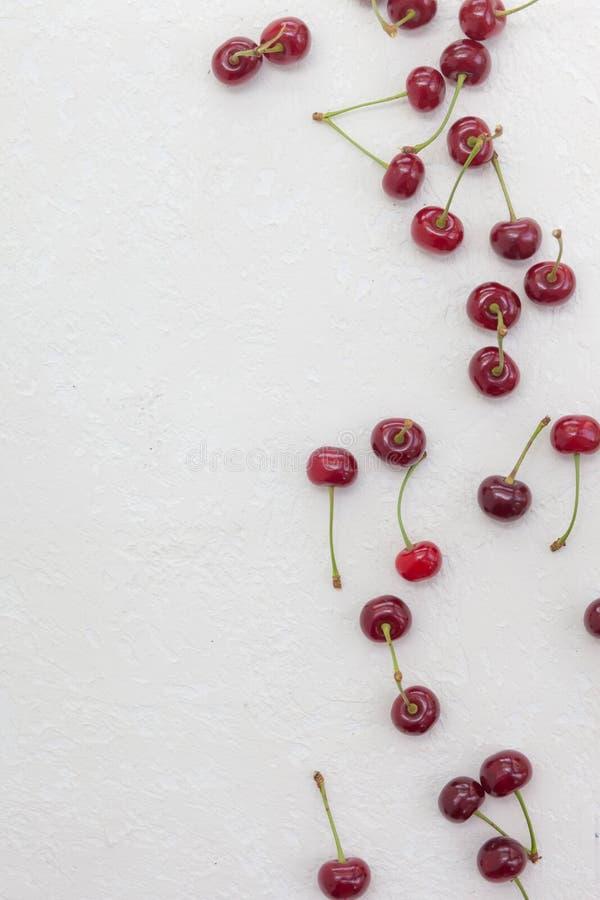 Cerejas grandes dispersadas em um fundo branco imagens de stock royalty free