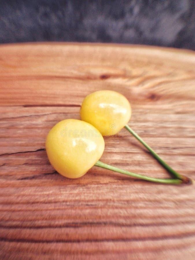 cerejas maduras amarelas na tabela de madeira fotografia de stock