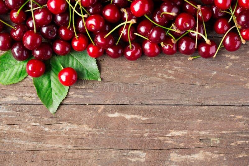Cerejas maduras na tabela de madeira imagem de stock royalty free