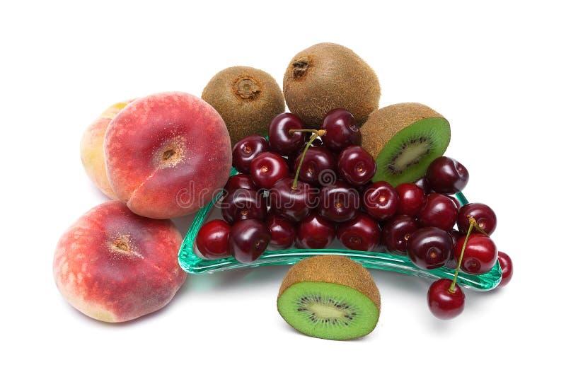 Cerejas, pêssegos e close up maduros do quivi em um fundo branco fotos de stock