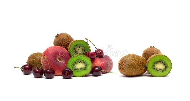 Cerejas, quivi e pêssegos maduros em um fundo branco imagem de stock