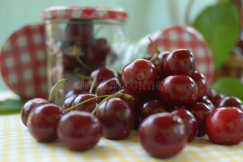 Cerejas vermelhas com as hastes na toalha de mesa amarela fotos de stock royalty free