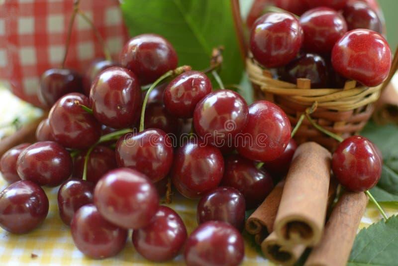 Cerejas vermelhas com hastes e hastes da canela na frente da cesta do litlle imagens de stock royalty free
