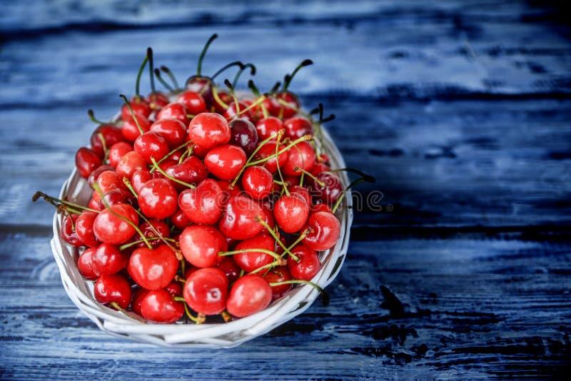 Cerejas vermelhas em uma tabela de madeira imagem de stock