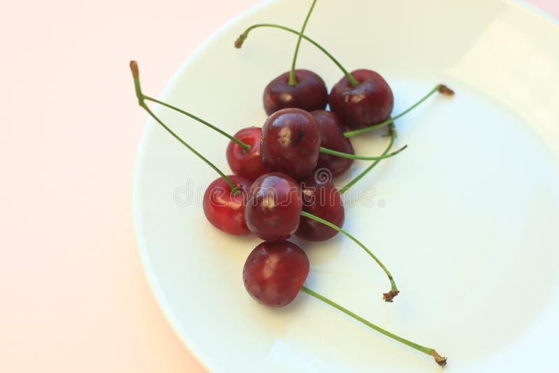 Cerejas vermelhas frias frescas na placa branca no close-up cor-de-rosa do fundo do pó Espaço da cópia, estilo minimalistic imagem de stock royalty free