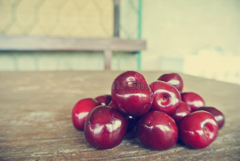 Cerejas vermelhas maduras na tabela de madeira rústica; retro filtrado foto de stock