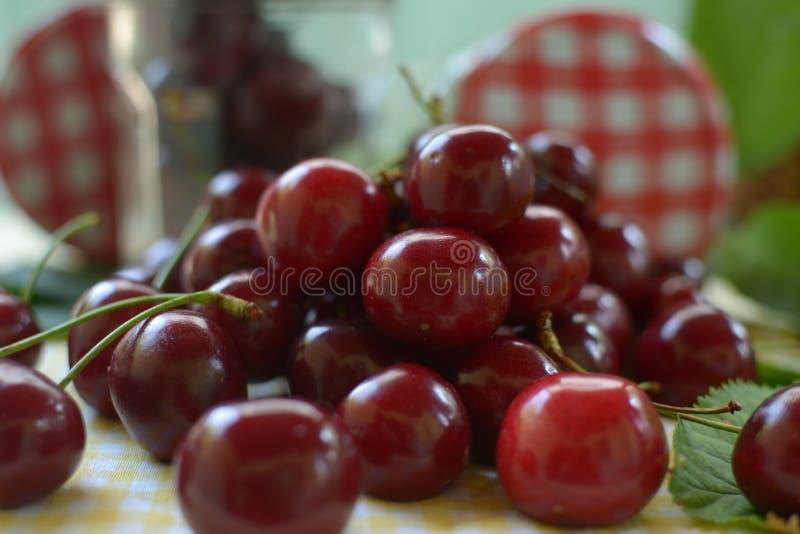 Cerejas vermelhas na toalha de mesa amarela e no tampão vermelho dos frascos foto de stock