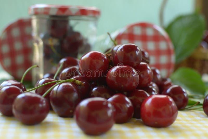 Cerejas vermelhas na toalha de mesa amarela e no tampão vermelho dos frascos imagens de stock royalty free