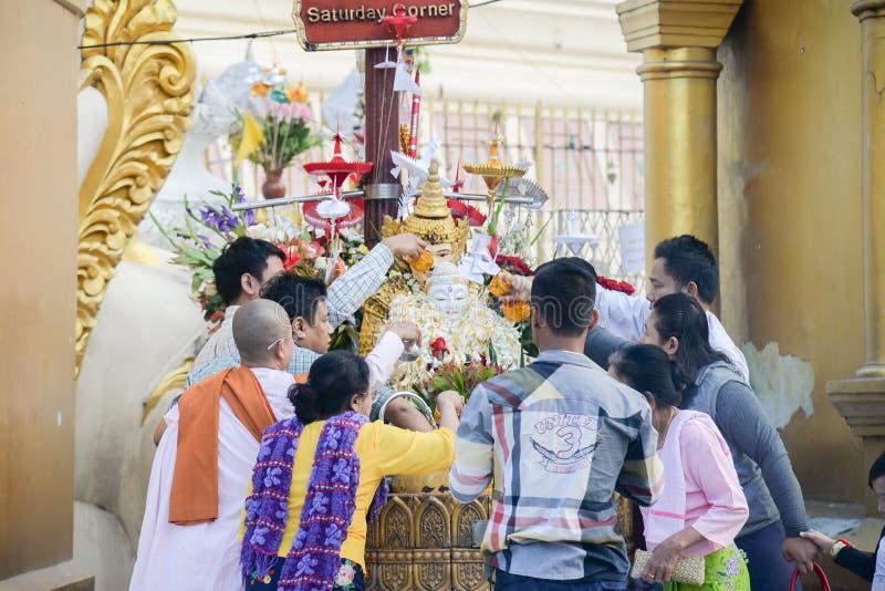 Ceremoni för vatten för buddistmyanmar folk hällande på den buddha bilden med en bön och en önska i shwedagonpagod på 17 December arkivbilder