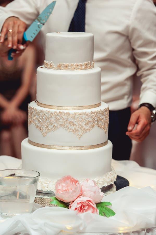 Ceremonia de boda la novia y el novio hacen su primer caso juntos, cortaron el pastel de bodas fotos de archivo libres de regalías