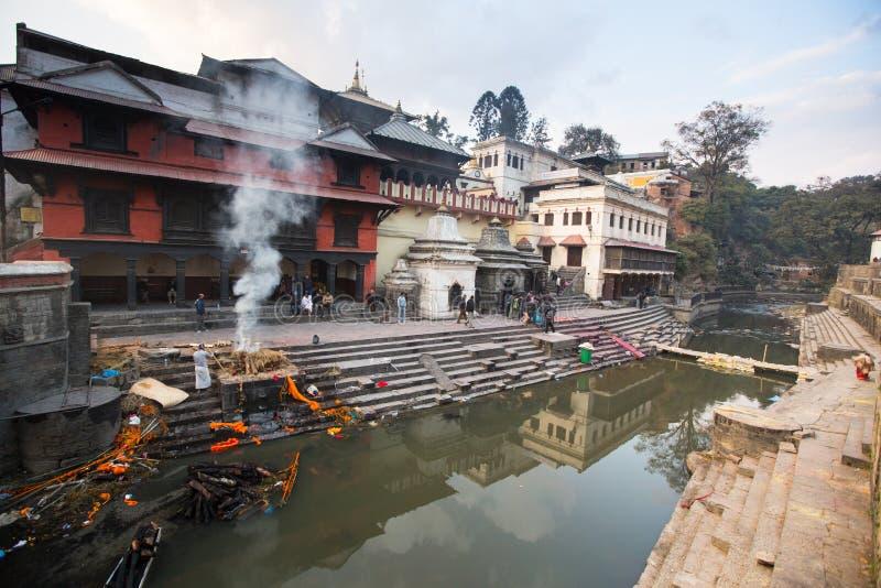 Ceremonia de la cremación a lo largo del río santo de Bagmati en Bhasmeshvar Ghat en el templo de Pashupatinath fotos de archivo libres de regalías