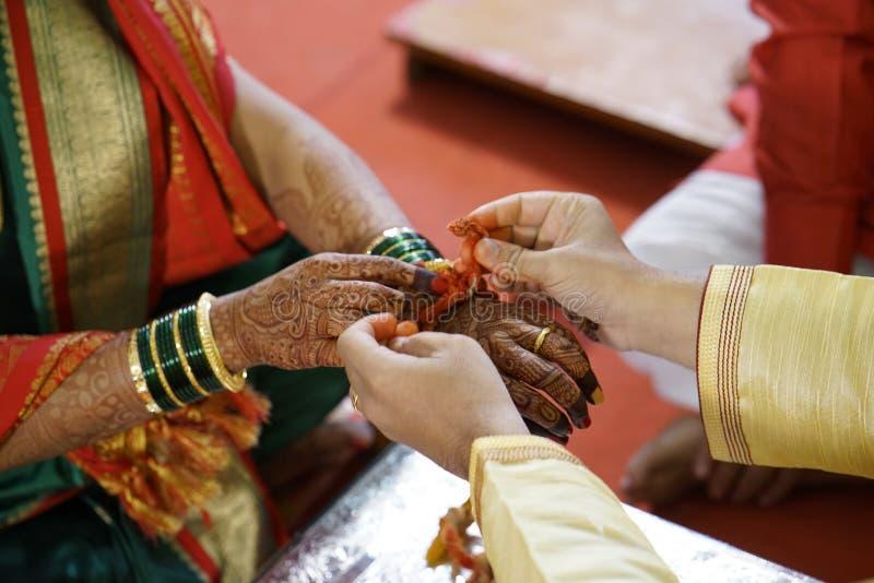 Ceremonia de matrimonio hindú tradicional donde hilo santo de las mareas del novio en la muñeca de la novia imagenes de archivo