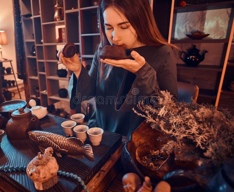 Ceremonia de té china El amo oriental que lleva un vestido gris que sostiene una tetera y respira el aroma del té natural fresco foto de archivo libre de regalías