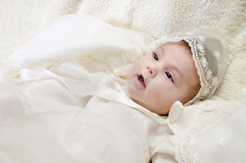 Ceremonial clothes and baby. Little baby with ceremonial cap, christening clothes royalty free stock image