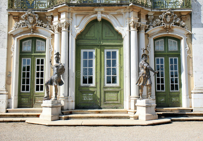 Ceremonial facade of the National Palace, Queluz. Bronze statues near the entrance of the Ceremonial Facade of the corps de logis of the Rococo Baroque style royalty free stock photos