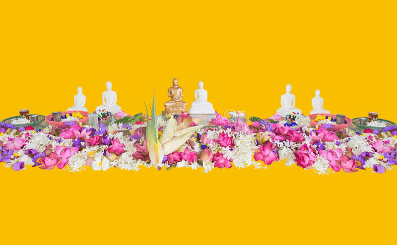 Ceremonial flowers and buddha figurines. Isolated on yellow background royalty free stock images