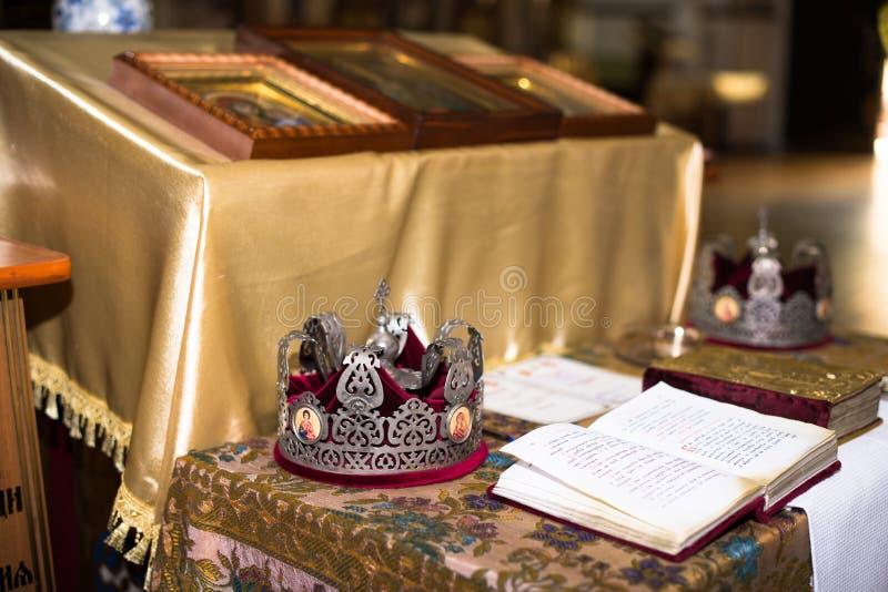 Ceremonie van het huwelijk in de Russische Orthodoxe Kerk De kronen liggen dichtbij bijbel dichte omhooggaand stock fotografie