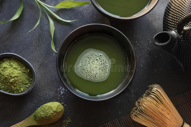 Ceremony green matcha tea and bamboo whisk on black table. Top view. Space for text. Ceremony traditional green matcha tea and bamboo whisk on black table. Top stock image