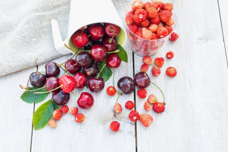 Cereza dulce madura y fresa salvaje en un círculo en un fondo de madera blanco imagen de archivo libre de regalías